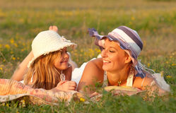 Mother and daughter lying on the meadow Stock Images