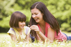 Mother and daughter lying outdoors with flower Stock Images