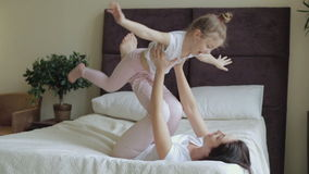 Mother and daughter lying and playing on the bed at home stock footage