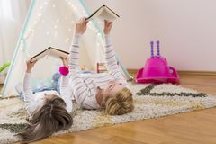 Mother and daughter reading books. Mother and daughter lying on a playroom floor, reading books. Focus on the mother stock images