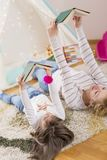 Reading a fairy tale. Mother and daughter lying on a playroom floor, reading books stock photography