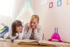 Storytelling. Mother and daughter lying on a playroom floor, reading a fairy tale. Focus on the mother royalty free stock photos