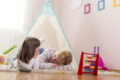 Mother and daughter playing. Mother and daughter lying on a playroom floor, speaking to each other and relaxing. Focus on the mother royalty free stock photography
