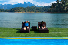 Mother and daughter lying relaxing at the pool, on the lake. Royalty Free Stock Photo