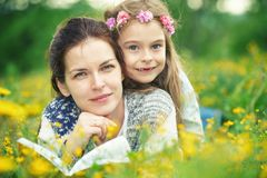 Mother and daughter reading book on green spring meadow Stock Photo