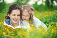 Mother and daughter reading book on green spring meadow Royalty Free Stock Photo