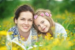 Mother and daughter reading book on green spring meadow Stock Images