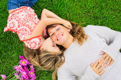 Mother and daughter lying together outside on grass Royalty Free Stock Photography