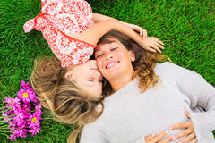 Mother and daughter lying together outside on grass Stock Photo