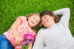 Mother and daughter lying together outside on grass Stock Photos