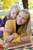 Mother and daughter lying under autumn tree Royalty Free Stock Photography