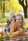 Mother and daughter lying under autumn tree Stock Image