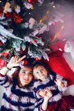 Mother and daughter lying under the Christmas tree. In the same clothes sweaters Stock Photo