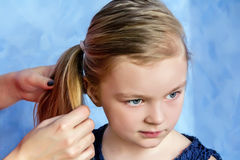 Mother and daughter makes hairstyle Stock Photos