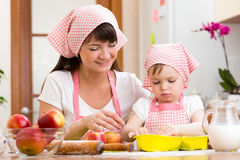 Mother and daughter making apple pie together. Mother and daughter making apple pie Royalty Free Stock Photos