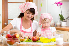 Mother and daughter making apple pie together. Mother and daughter kid making apple pie together Royalty Free Stock Images