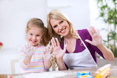 Mother and daughter making bread and showing hands Royalty Free Stock Photography