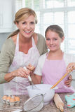 Mother and daughter making cake together Royalty Free Stock Image