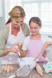 Mother and daughter making cake together Royalty Free Stock Photography