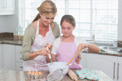Mother and daughter making cake together Stock Photos