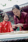 Mother and daughter making dumplings in traditional clothing Royalty Free Stock Photography