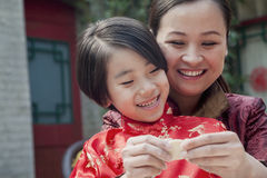 Mother and daughter making dumplings in traditional clothing, close up Stock Images