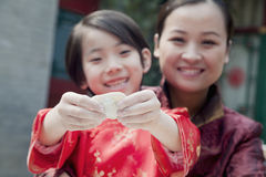 Mother and daughter making dumplings in traditional clothing, close up Stock Photo