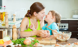 Mother with daughter making fish dumplings Stock Photography