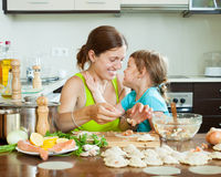 Mother with daughter  making fish dumplings at home kitchen Royalty Free Stock Images