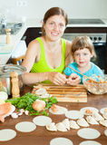 Mother with daughter making fish dumplings in a home large kitch Stock Photo