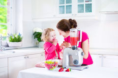 Mother and daughter making fruit juice stock images