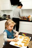 Mother and daughter making gingerbread cookies at home stock image