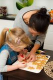Mother and daughter making gingerbread cookies at home Royalty Free Stock Photography