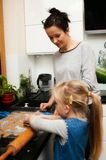 Mother and daughter making gingerbread cookies at home royalty free stock photos