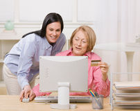 Mother and daughter making online purchase. Adult mother and daughter making online purchase with credit card at home Royalty Free Stock Photography