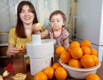 Mother and daughter making  orange juice Royalty Free Stock Photo