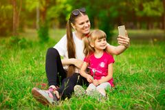 Mother and daughter making a selfie in park stock photography