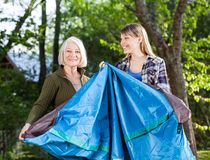 Mother And Daughter Making Tent In Park At Stock Photos