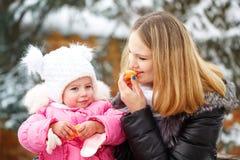 Mother and daughter mandarin. Winter fun. Royalty Free Stock Photography
