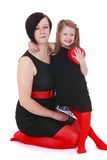 Mother and daughter in matching. Black and red outfits look very impressive in the Studio on a white background Stock Images