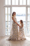 Mother and daughter in matching dresses standing Stock Photography