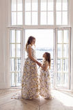 Mother and daughter in matching dresses standing stock photos