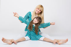 Mother and daughter in matching outfit having fun. Happy mother and daughter sitting on the floor wearing matching outfit with bare feet having fun holding hands royalty free stock images