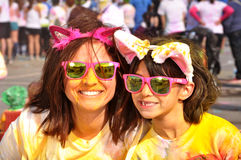 Mother and daughter in matching pink sunglasses and animal ears after a color run Stock Image