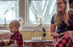 Mother and daughter in matching plaid pajamas on Christmas morni royalty free stock photography