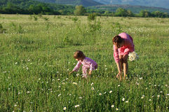 Mother and daughter on meadow Stock Photos