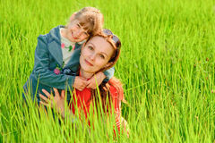 Mother and daughter on meadow. The little girl embraces mother on a summer green field Stock Image