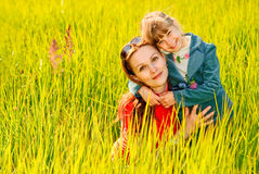 Mother and daughter on a meadow. The little girl embraces mother on a summer green field Stock Photo