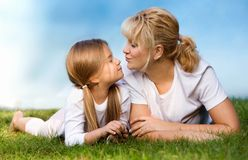 Mother and daughter at the meadow. Mother kissing her daughter at the park or meadow