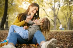 Mother and daughter in meadow. Mother and daughter having fanny. Conversation in park.Lifestyle stock images